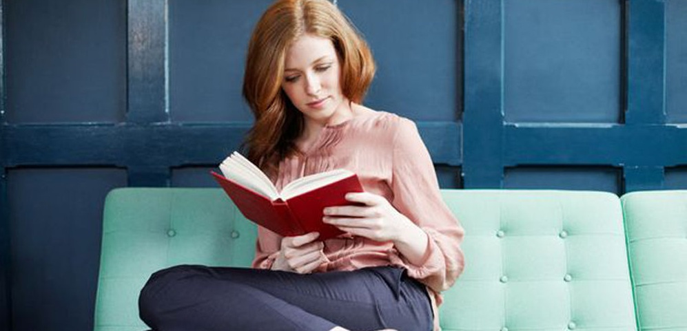 Woman-reading-a-book-on-sofa-2043550-2